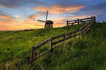 Holländische Mühle mit Zaun bei Sonnenuntergang