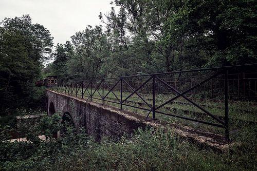 Een oude brug met een vergaande trein aan het eind van het spoor