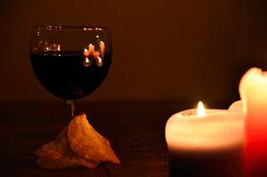 Wijn in wijnglas en chips bij kaarslicht.
