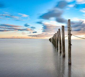 Lange Belichtungsstangen im Sonnenuntergang im Meer von Marjolein van Middelkoop