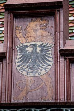 Schild met leeuw boven op dak van het Raadhuis van Bazel in Zwitserland van Joost Adriaanse