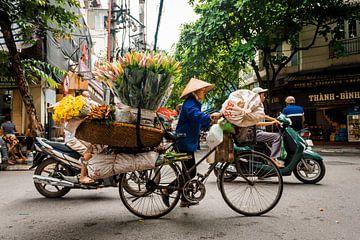 Vrouw met fiets vol met bloemen in Hanoi Vietnam. van Niels Rurenga
