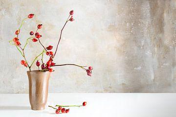 Branches d'églantier dans un vase en grès sur une table blanche devant un mur d'époque, belle décora sur Maren Winter