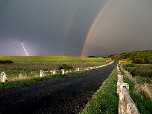 Contrating landscape in hungary with dramatic weather and rainbow.