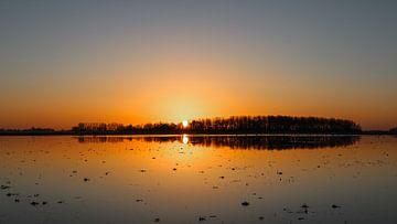 Sonnenaufgang auf einem überschwemmten Stück Land von Karin Bijpost