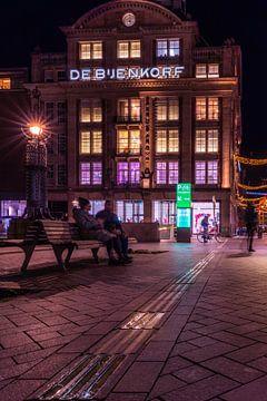 Mensen voor de Bijenkorf in Amsterdam in de avond van Bart Ros