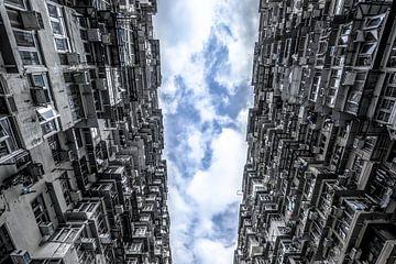 Blauwe lucht met wolken tussen de stad van Mickéle Godderis