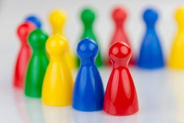 Conceptuele gekleurde speelpionnen in een rij van Tonko Oosterink