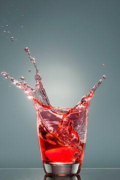 Spetters uit een glas met rode vloeistof