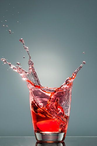 Spetters uit een glas met rode vloeistof van