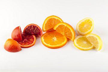 Schijfjes en partjes citrusfruit tegen een lichte achtergrond. van Ans van Heck