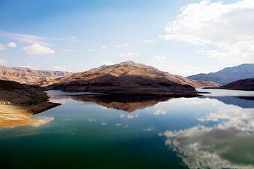 Roodbruine rotsen en wolkenlucht gespiegeld in een meer in Jordanië van WorldWidePhotoWeb