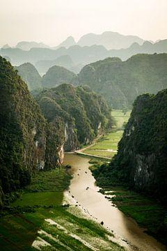 Viewpoint in Tam Coc Vietnam met een heuvelachtig landschap en bootjes in het water. van Twan Bankers