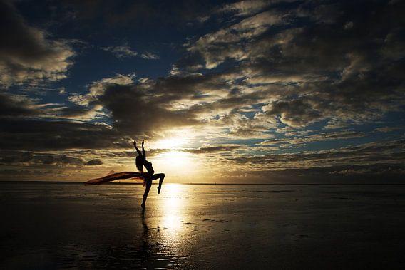 Artistiek naakt op het wad met een doek bij zonsondergang van Arjan Groot