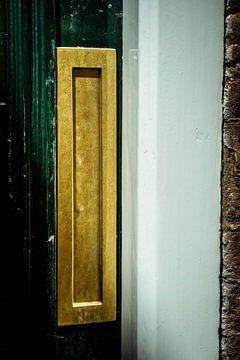 Gouden verticale brievenbus in de deur, een traditionele manier om brieven aan een huis te bezorgen.