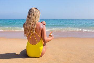 Junge Frau am Strand mit Meer schmiert sich mit Sonnencreme von