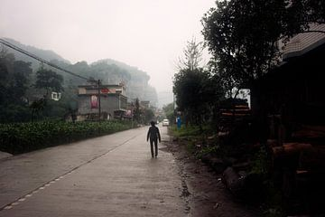 Chinese boer op regenachtige dorpsweg van André van Bel
