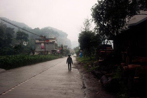 Chinese boer op regenachtige dorpsweg