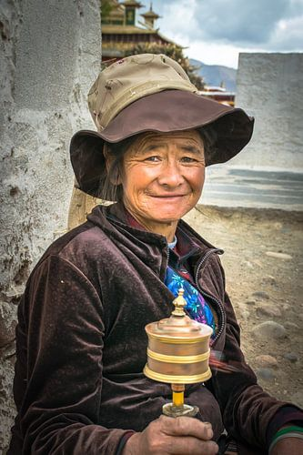 Tibetaanse vrouw met draaiende gebedsmolen, portret