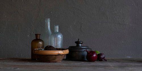 Modern stilleven met glas, tin, uien en limoen