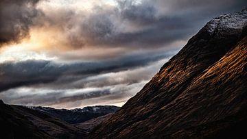 der Himmel hängt bedrohlich über den Bergen, voller Hoffnung am Ende eines schönen Tages von Studio de Waay