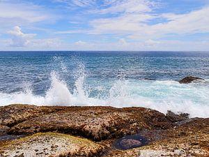 Ozean Welle die gegen einen Felsen prallt - weiße Gischt vor türkisblauem Wasser