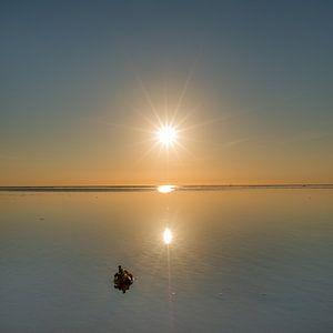 Een spiegelende Waddenzee tijdens zonsondergang vanaf de pier van PaesensModdergat