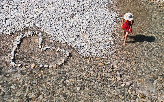 Hart gelegd in stenen op keienstrand, dame met hoed in rood van Beeldig Beeld