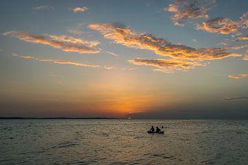 Menschen auf einem Floß, die die untergehende Sonne anstarren von Menno van der Haven