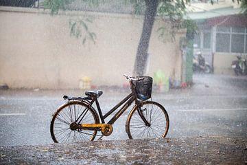 Fiets in de regen in Hanoi van ard bodewes