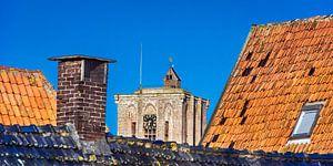 Kerk top in Elburg tussen de daken van enkele huizen.