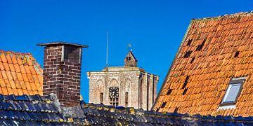 Kerk top in Elburg tussen de daken van enkele huizen. van