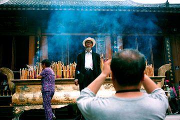 Oude man in rokerige Chinese tempel von André van Bel