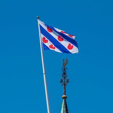 De Friese vlag en de kerktorenspits van het dorpje Cornwerd van
