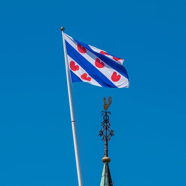 De Friese vlag en de kerktorenspits van het dorpje Cornwerd van Harrie Muis