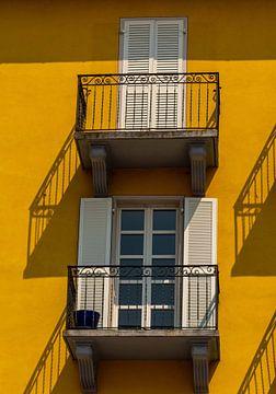 Balkons tegen gele muur met schaduw van Martine Moens