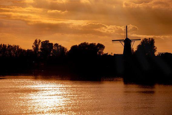 Avondlucht met zon op het water en een Windmolen.