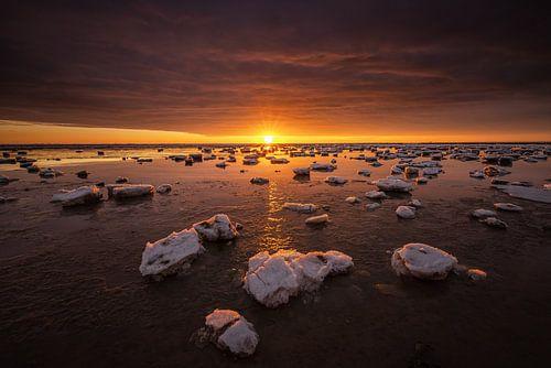 De Waddenzee is bedekt met IJsschotsen in de winter. Een mooie zonsondergang geeft prachtige kleuren