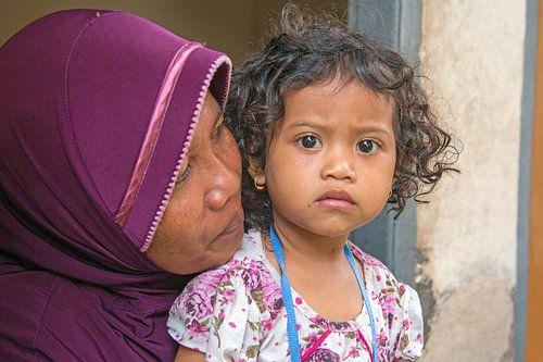 Traditioneel geklede indonesische vrouw met haar kind
