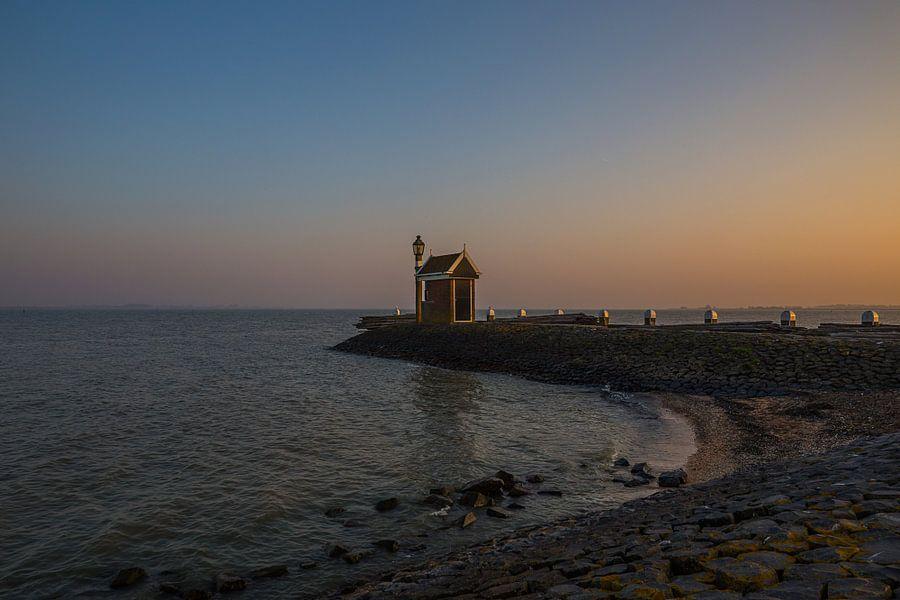 Alleenstaand huisje aan de Volendamse haveningang bij zonsondergang