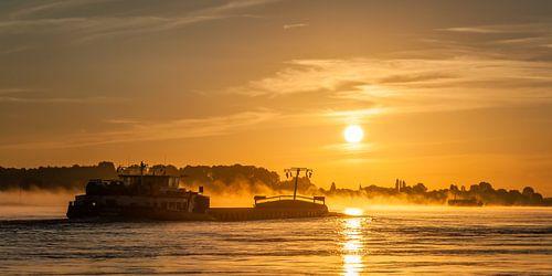 Panorama: Ein Schiff auf dem Fluss Waal mit aufgehenden Sonne von John Verbruggen