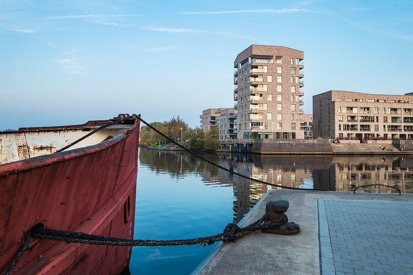 Modern buildings and vessel in the city Rostock, Germany van Rico Ködder