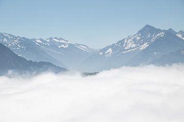 Begrtoppen steken boven de wolken uit. van Sasja van der Grinten