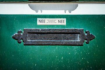 Oude horizontale brievenbus in een groene deur, nederlandse sticker die nee zegt tegen reclame en fo