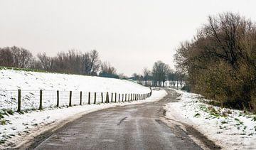 Landweg in een sneeuwlandschap van Ruud Morijn