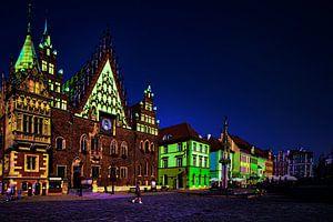 Zicht op een plein met felgekleurde gebouwen bij avond