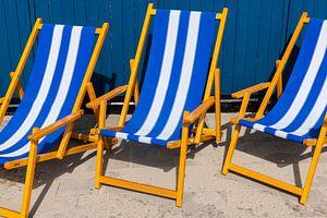 Blauwe ligstoelen op terras van