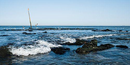 Zeezicht met golfbreker vanaf het strand van Scheveningen