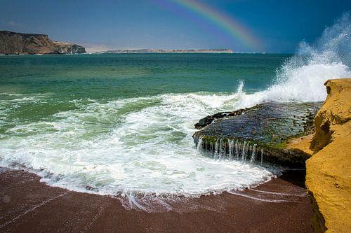 Branding bij het rode strand van het schiereiland Paracas met regenboog, Peru