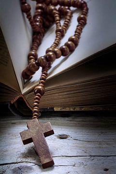 katholieke houten rozenkrans met kruis in een oud boek over rustiek vintage hout, religieus symboolc van Maren Winter